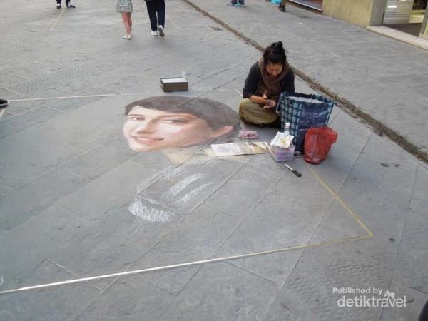 Pelukis jalanan sedang membuat karya yang cantik
