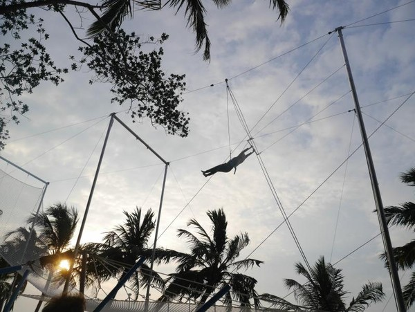 Flying trapeze dengan latar belakang sunset
