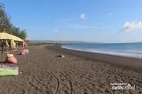 Garis pantai yang memanjang dengan pepohonan di sebelah kirinya sungguh indah, terlebih saat sore hari
