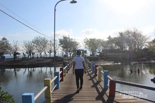 Melewati jembatan kayu yang menjadi penghubung Pulau Santen.