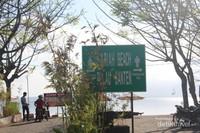 Sebuah tanda cukup besar bagi pengunjung pria dan wanita terdapat di dekat tempat parkir kendaraan roda dua.