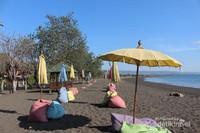 Pemandangan pantai bagi pengunjung wanita dengan bangku dan payung warna warni.