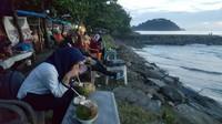 Menikmati kelapa muda alami di pesisir pantai Padang. Memandang lepas pantai dan merasakan kesegaran air kelapa muda.