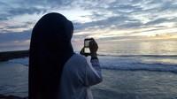 Tak ingin menyia -nyiakan keindahan matahari tengelam, kamu bisa mengabadikan lewat bidikan kamera ponsel dan mengukir cerita lewat sosial media tentang senja di pesisir pantai Padang