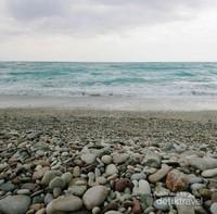 Pemandangan laut lepas dan kerikil-kerikil penuh warna di Pantai Kolbano.