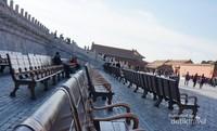 Deretan bangku di halaman istana dengan beberapa pengunjung menikmati suasana Forbidden City