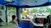 Bus attendant yang bertugas untuk mengatur naik turunnya penumpang dan memberikan informasi tentang destinasi wisata yang dilalui