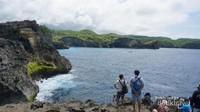 Sebagian wisatawan tengah menikmati panorama laut lepas dari tebing batu, cuaca panas tidak mengurangi antusiasme pengunjung karena pemandangannya memang luar biasa