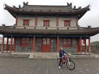 Berfoto di depan bangunan khas Tiongkok sambil bersepeda