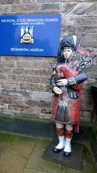 Patung dengan pakaian khas Skotlandia di depan Museum Resimen