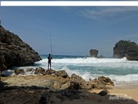 pemancing asik beradu dengan ombak