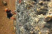 Seorang pemanjat sedang memperhatikan lubang-lubang tempat mencengkram agar saat ingin melanjutkan pendakian, pendaki lebih mudah untuk kembali memanjat.