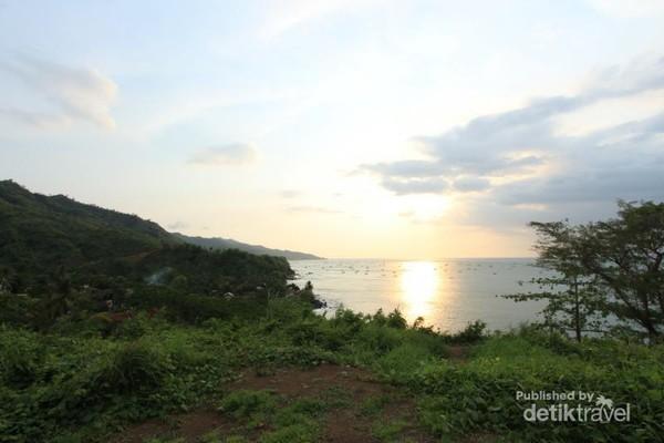Pantainya pun sungguh indah. Perpaduan bukit bukit hijau dengan birunya lautan