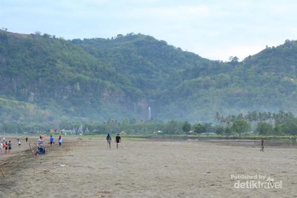 Dari bibir Pantai Palangpang deretan bukit dan air terjun sudah dapat terlihat