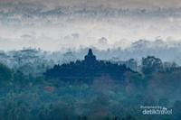 Tampak dari jauh Candi Borobudur diantara pepohanan dan embun pagi.