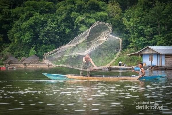 Di dalam foto seorang warga setempat sedang melempar jala untuk menangkap ikan bersama temannya yang mengatur posisi perahu kecilnya