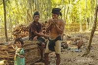Tiga orang suku kajang dalam sedang bersantai disekitar rumah saat sore hari. Umumnya suku kajang dalam bekerja sebagai petani.
