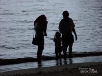 Siluet foto sebuah keluarga suami, istri, dan anak, yang sedang mengunjungi pantai di pantai Lamaru yang sedang mendung