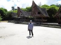 Berfoto dengan latar rumah tradisional Batak
