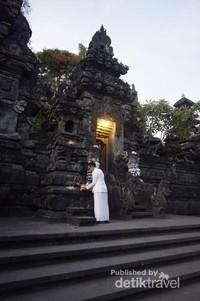 Seorang ibu sedang menaruh sesajen di gerbang Pura.