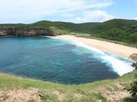 Pantai yang melengkung di lihat dari atas TWA Gunung Tunak