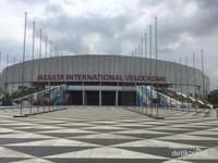 Kemegahan stadion dengan tiang-tiang bendera berada di bagian depan.