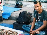Penjual batu akik menunggu orang membeli dagangannya