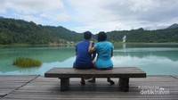 Pasangan suami istri nampak tengah menikmati keindahan danau.
