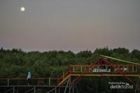 Seorang pengunjung sedang berjalan di jembatan penyebrangan saat hari mulai gelap di lokasi Ekowasita Mangrove Lantebung.