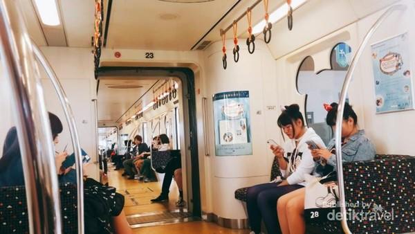 Penumpang dengan aksesoris unik ala Disney di dalam kereta commuter menuju Tokyo Disneysea.