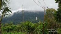 Dari kejauhan nampak salib besar yang seolah-olah menempel di bukit.