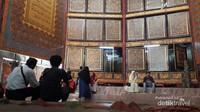 Beberapa orang pengunjung sedang duduk-duduk istirahat seraya tetap memandangi betapa besarnya Al-Quran di Al-Quran Al-Akbar