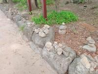 Deretan batu-batu yang disusun sedemikian rupa oleh pengunjung di sepanjang jalan menuju Patung Budha Besar sebagai bagian dari tradisi.