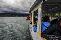 Seorang pengunjung berpose keluar jendela dalam perjalanan menuju Pulau Dutungan dengan latar belakang pegunungan kabupaten Barru.