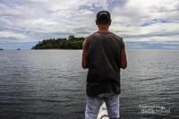 Seorang pemilik kapal sedang berdiri di bagian depan menghadap ke pulau dutungan.