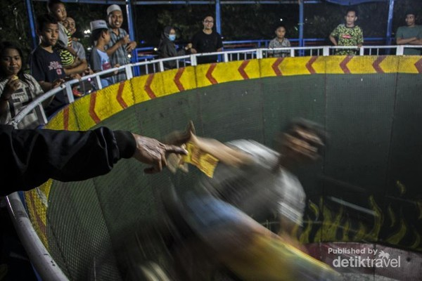 Seorang pengendara roda gila sedang mengendarai motornya sambil berusaha meraih uang yang diberikan oleh warga yang menyaksikan.