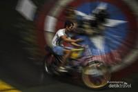 Terlihat seorang pengendara sedang mengendarai motornya dengan cepat di lintasan yang berbentuk tong raksasa.