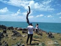 Anzani, melakukan swafoto dengan background laut lepas.