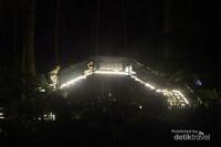 Jembatan kayu saat malam tiba juga dihiasi lampu-lampu.