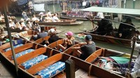 Wisatawan asing yang menggunakan jasa perahu untuk menyusuri pasar terapung ini