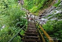 Jalur trekking menuju air terjun yang berupa tangga kayu, bambu, dan batu.