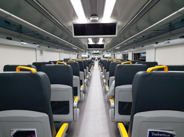 Deretan kursi di gerbong kereta bandara dengan kompartemen di atasnya