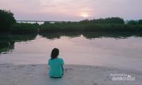 Menyaksikan matahari terbenam dengan duduk santai di pasir pantai.