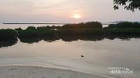 Air pantai yang tenang memantulkan matahari senja.