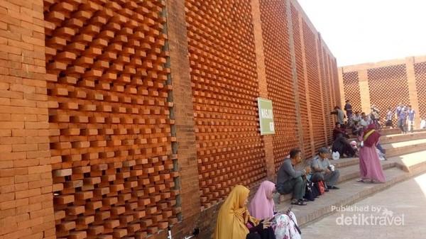 Tampak pengunjung beristirahat di dekat pintu masuk masjid.
