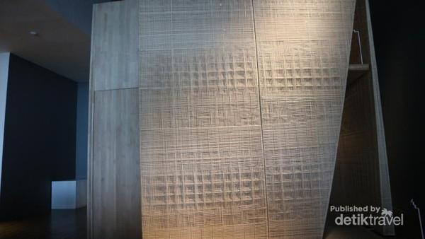 Dinding depan yang dilapisi anyaman rotan dengan motif kain tradisional Indonesia