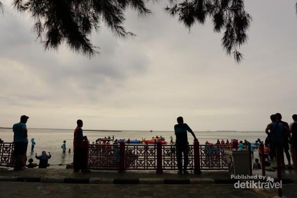 Pengunjung menunggu sunset di salah satu pantai.
