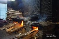 Tungku tanah dengan bahan bakar kayu untuk memasak ayam.
