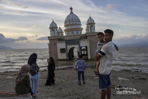 Beberapa masyarakat Kota Palu terlihat berdiri dihadapan reruntuhan Masjid Arqam Bab Al Rahman. Bekas rumah ibadah itu kini menjadi saksi keteguhan masyarakat disana yang berupaya bangkit dari sebuah tragedi.