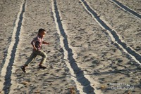 Anak kecil berlarian di antara garis shaf sholat.